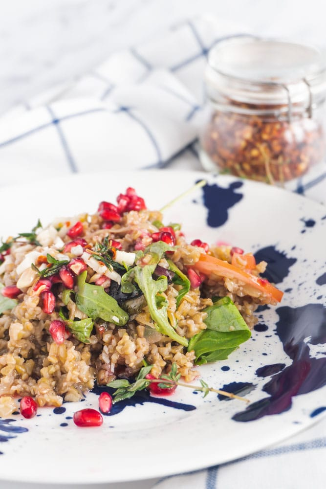 Pomegranate salad with a pot of chilli flakes